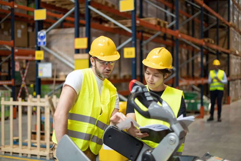 Employees consult while working in the warehouse